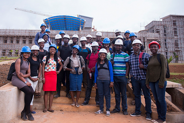 Student group photo at construction site of new campus